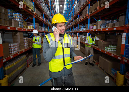 Warehouse worker talking on mobile phone and holding clipboard - Stock Image