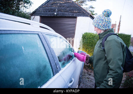 White middle-aged woman in a bobble hat with a pink mitten ice scraper clears the ice off her silver car before - Stock Image