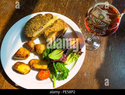 Café lunch a Cheddar cheese and red onion sandwich  on brown bread with salad sesame potatoes and a glass of organic Pale Ale - Stock Image