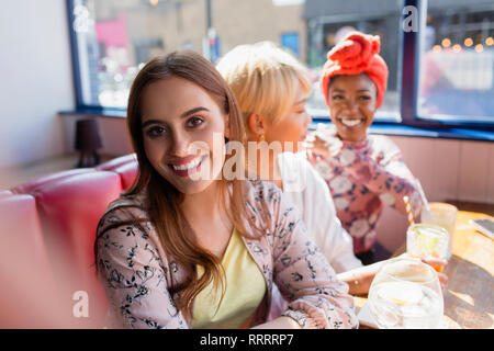 Portrait smiling young woman in sunny restaurant with friends - Stock Image