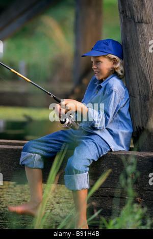 Boy fishing under bridge - Stock Image