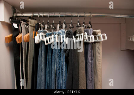 Pairs of jeans and pants hang on hangers in a row in the closet, well organized - Stock Image