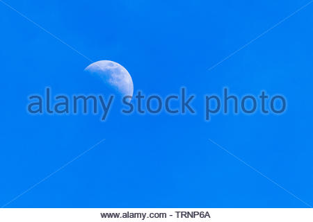 A zoom to the moon (Earth's natural satellite) during the daytime. The sky is clear blue and there are no people in the vibrant color image - Stock Image