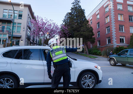 VANCOUVER, BC, CANADA - APR 20, 2019: A Vancouver Traffic Authority officer providing assistance to a motorist. - Stock Image