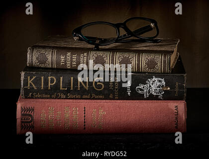 Three stacked vintage classic books closed on a desk with reading glasses on top - classic litereracy concept - Stock Image