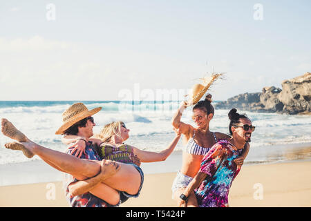 Cheerful group of people boys and girls have fun together at the beach during summer holiday vacation - men carrying women - coloured clotehs for outd - Stock Image