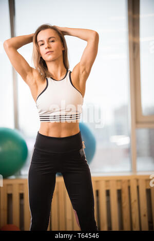 Young athletic blonde woman standing in the fitness studio - Stock Image