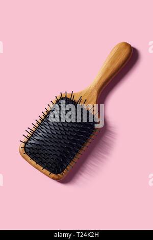 Bamboo Paddle Hair Brush On Pink Background - Stock Image