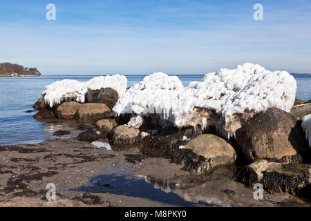 Melting ice formations on boulders at the coast at Skodsborg just north of Copenhagen, Denmark, on an early, sunny - Stock Image