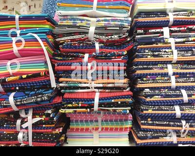 A full frame background of colourful, stacked fabric, textiles and fashion material on a retail store shelf - Stock Image