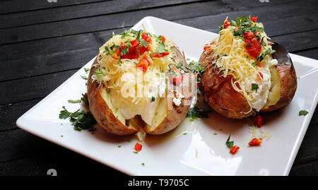 Close up of a hot baked potato topped with sour cream, green onions and cheese on black wooden board - Stock Image