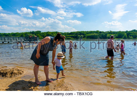 Woman and small child with hat walking close by - Stock Image