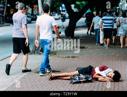 Rio de Janeiro, Brazil, March 23, 2019: Homeless young man sleeping rough while pedestrians walk next to him on busy pedestrian sidewalk in the wealth - Stock Image