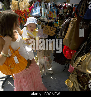 Mother and toddler shopping for bags, Mijas Pueblo, Costa del Sol, Andalucia, Spain - Stock Image