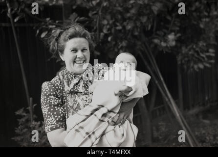 1930s, happy lady in spotted dress holding her baby. - Stock Image