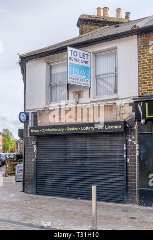 Closed newsagent and corner shop with estate agent's To Let sign. - Stock Image