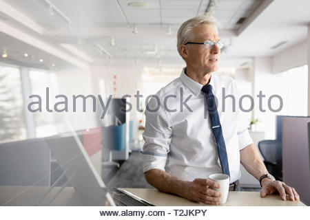 Thoughtful businessman drinking coffee in office - Stock Image