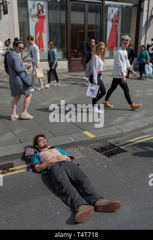 Passers-by look down on a young campaigner resting with his head on an Oxford Circus kerb on day 4 of protests by climate change environmental activists with pressure group Extinction Rebellion, on18th April 2019, in London, England. - Stock Image