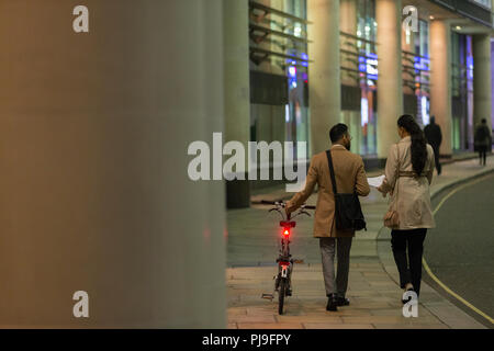 Business people with bicycle walking on urban sidewalk at night - Stock Image