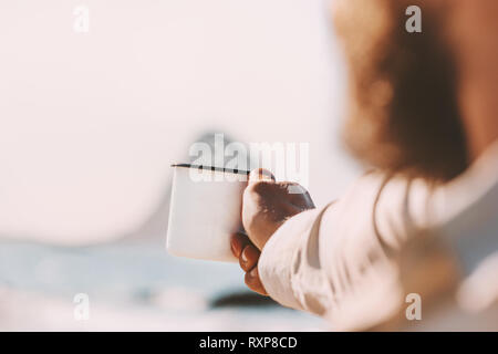 Outdoor travel vacations man hand holding metal mug relaxing at ocean beach white tea cup picnic lifestyle adventure - Stock Image