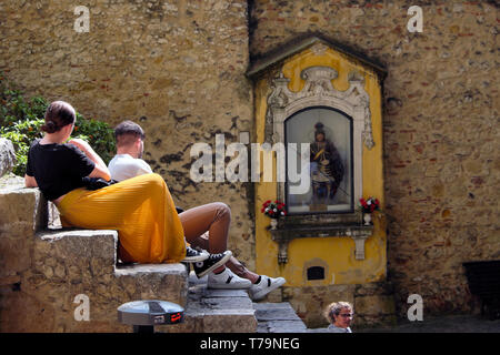 Tourists sitting on steps by the statue of St George shrine at the Castelo de Sao Jorge Lisbon Castle in Lisbon Portugal Europe EU  KATHY DEWITT - Stock Image