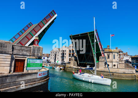Weymouth harbour bridge raised to allow a yacht passage, Dorset, UK. - Stock Image