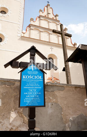 Informational church cross in Janowiec village, Poland, Europe, blue board with mass schedule information in front - Stock Image