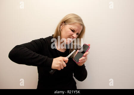 Woman is determined to break into her cell phone with a hammer - Stock Image