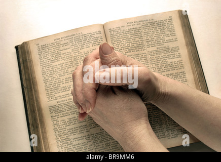 Woman hands on vintage Bible - Stock Image