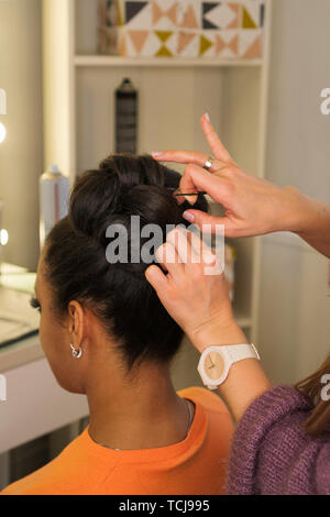 Hair stylist hands form high hairstyle on head of young African American. Pinning curls with hairpins and hair slide. Master class on creating high ev - Stock Image