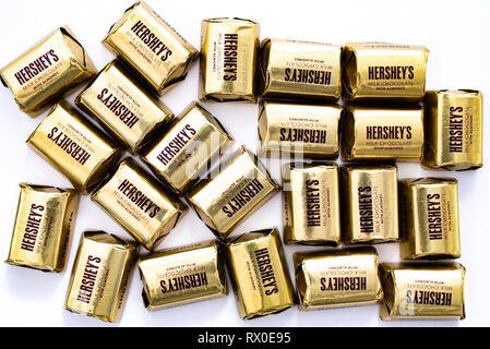 A pile of Hershey's Milk Chocolate with Almonds Nuggets in individual gold colored wrappers isolated on white. - Stock Image
