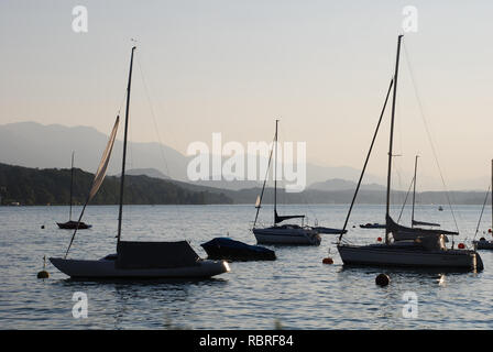 Austria, silhouettes of sailing yachts, moored on the lake against the mountains - Stock Image