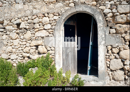 Dilapidated stone built house and arch Crete Greece - Stock Image