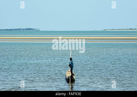 A man travels by dugout canoe in the Turtle Islands, Sierra Leone - Stock Image