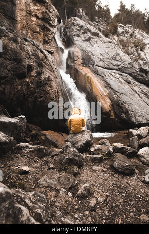 Single man standing near gollinger waterfall in austria. Travel summer alps concept. - Stock Image