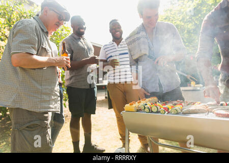 Male friends drinking beer around barbecue grill in backyard - Stock Image