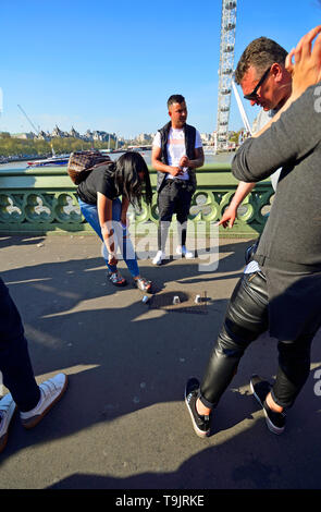 London, England, UK. Illegal Cup and Ball / 3 Cups Trick on Westminster Bridge, trying to con money from passing tourists on a Bank Holiday - Stock Image