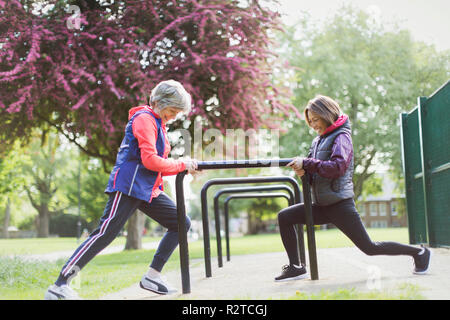 Active senior female runners stretching legs in park - Stock Image
