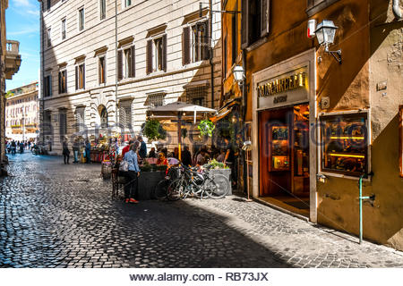 Tourists enjoy shopping and lunch at a sidewalk cafe on a narrow cobblestone street in the historic center of Rome, Italy - Stock Image