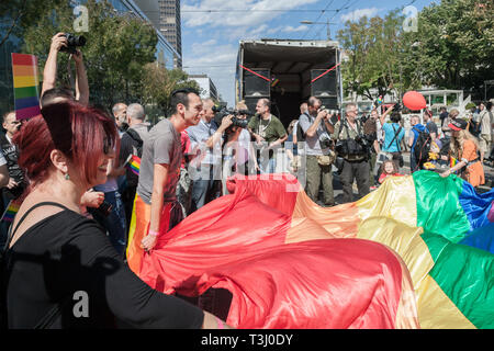 BELGRADE, SERBIA - SEPTEMBER 17, 2018:  Activists waiving a huge gay rainbow flag surrounded by journalists during the Belgrade Gay Pride. The parade  - Stock Image
