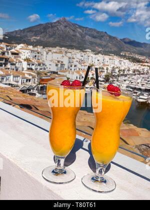 Puerto Banús Marbella fresh natural Spanish orange juice glasses, on luxury alfresco bar Hotel terrace overlooking marina Puerto Banús Marbella Spain - Stock Image