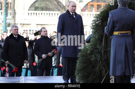 Moscow, Russia. 23rd Feb, 2019. Russian President Vladimir Putin during a wreath ceremony at the Tomb of the Unknown Soldier at the Kremlin Wall to honour the memory of fallen soldiers on Defender of the Fatherland Day February 23, 2019 in Moscow, Russia. Prime Minister Dmitry Medvedev, center, and Speaker of the Duma Vyacheslav Volodin, left, stand behind. Credit: Planetpix/Alamy Live News - Stock Image