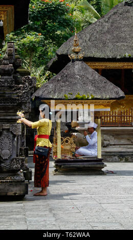 Prayer leader in a small cabin behind a woman putting out flower offerings in the foreground, Pura Tirta Empul temple, Ubud, Indonesia - Stock Image