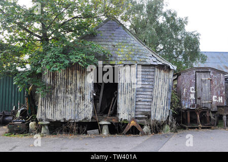 Old farm grain store on staddle stones.Wood and corrugated iron construction. Slate roof and shed full of old tools.Old wheeled shepherds hut Purbeck, - Stock Image
