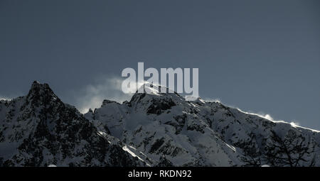 Wind blowing over snow capped mountain peaks. - Stock Image