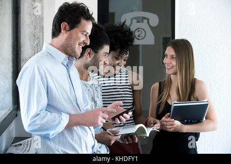 Group of friends standing around chatting - Stock Image