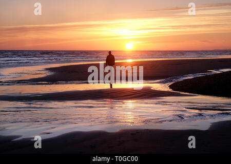 A solitary unrecognizable man standing on a deserted sandy beach, he is looking at a yellow sun setting over the sea the image has an orange glow, Bri - Stock Image