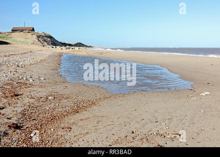 A view of the beach with a pool left by an ebbing tide in East Norfolk at Winterton-on-Sea, Norfolk, England, United Kingdom, Europe. - Stock Image