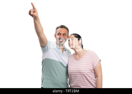 Smiling pointing index finger at above corner and woman looking with curious expression as couple concept isolated on white - Stock Image