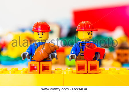 Poznan, Poland - February 15, 2019: Lego toy construction workers with safety helmet having a break while sitting on yellow blocks eating a croissant  - Stock Image